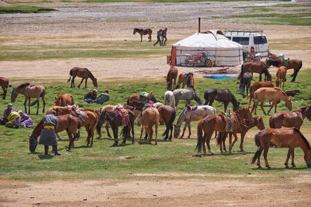 KHOVD, MONGOLIA - JULY 06, 2017: Mongolian nomad camp. Horses and car near traditional mongolian yurt.