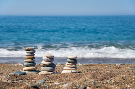 Stack of stones on Petra tou Romiou or Aphrodite Rock Beach, Cyprus. Stones pyramid on pebble beach with sea and blue sky on background. 免版税图像