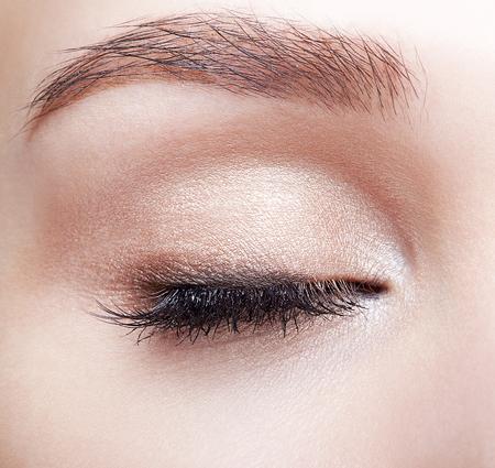 Nahaufnahmemakroaufnahme des geschlossenen menschlichen Frauenauges. Frau mit natürlichem Augen-Make-up Standard-Bild