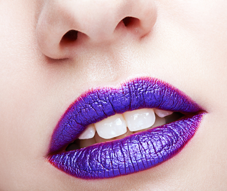 Closeup shot of human female face. Woman with violet lips makeup and white dentes. Imagens