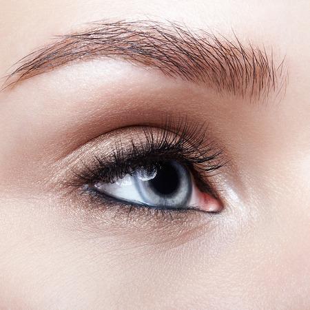 Nahaufnahmemakroaufnahme des blauen Auges der menschlichen Frau. Frau mit rauchigen Augen Make-up