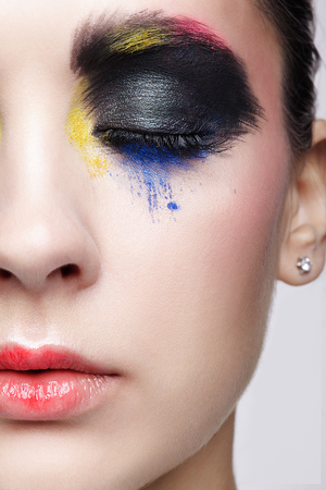 Close-up macro portrait of beautiful woman face make up. Female closed eye with unusual artistic painting makeup and red lips Stock Photo