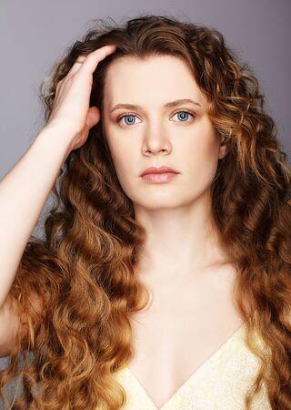 Portret młodej kobiety rasy kaukaskiej z falowanymi włosami na szarym tle. Dziewczyna długie złote kręcone włosy.