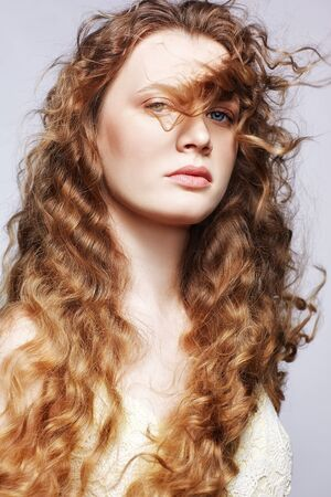 Portrait of a young caucasian woman with wavy hair on a gray background. Girl long golden curly hair.