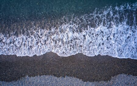 Aerial image of pebble beach natural background. Camera looks straight down. Crete, Greece