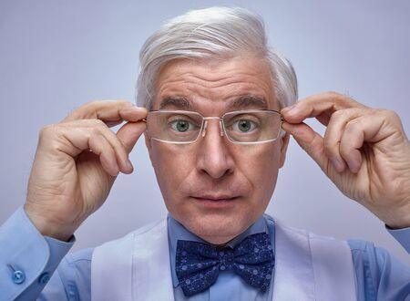 Close up portrait of senior businessman commis avec les yeux grands ouverts regardant la caméra avec surprise. Homme d'âge moyen adulte avec des lunettes dans les mains posant sur fond gris Banque d'images