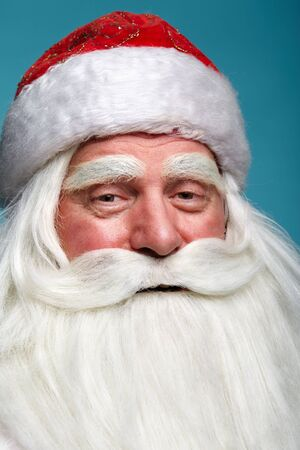 Close-up christmas face portrait of russiad Santa Claus Ded Moroz looking ironically squinting at the camera. White-haired elderly man with white beard and moustache on blue dackground. Stock Photo