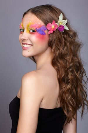 Portrait of happy smiling teen girl. Young female with unusual stylish make-up and false fashion feather eyelashes. Orchid flower in wavy hair.