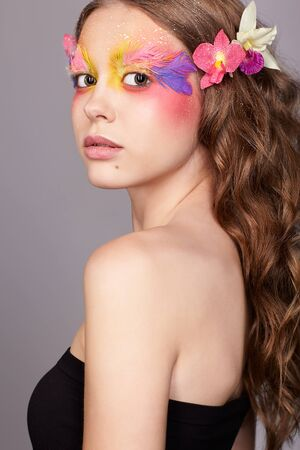Portrait of teen girl. Young female with unusual stylish make-up and false fashion feather eyelashes. Orchid flower in wavy hair. Фото со стока