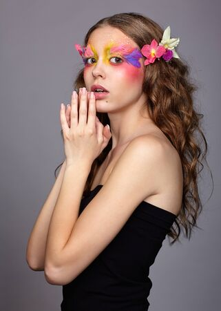 Portrait of teen girl with hand near face and orchid flower in wavy hair. Young female with unusual stylish make-up and false fashion feather eyelashes. Reklamní fotografie - 130126410