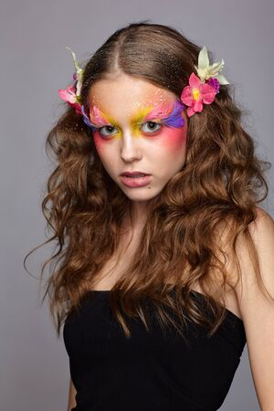 Portrait of teen girl with orchid flower in wavy hair. Young female with unusual stylish make-up and false fashion feather eyelashes. Reklamní fotografie - 130126416