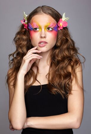 Portrait of teen girl with hand near face and orchid flower in wavy hair. Young female with unusual stylish make-up and false fashion feather eyelashes. Reklamní fotografie - 130126417