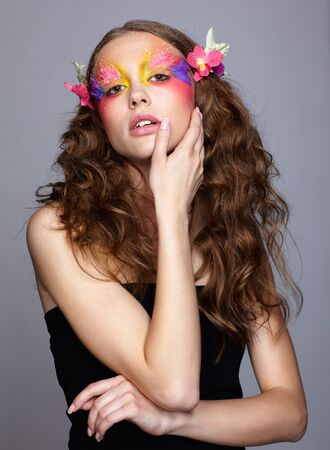 Portrait of teen girl with hand near face and orchid flower in wavy hair. Young female with unusual stylish make-up and false fashion feather eyelashes. Reklamní fotografie - 130126425