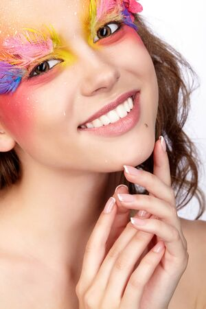 Portrait of happy smiling teen girl with hands near face. Young female with unusual stylish make-up and false fashion feather eyelashes. Orchid flower in wavy hair.
