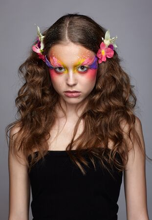 Portrait of teen girl with orchid flower in wavy hair. Young female with unusual stylish make-up and false fashion feather eyelashes.