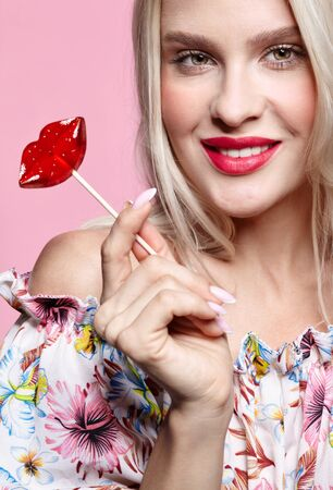 Portrait of blonde happy smiling woman with candy in hand. Red female lips shape lollipop. Sweet tooth concept.