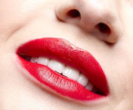 Ritratto a macroistruzione del primo piano della parte femminile del fronte. Sorridere rosso della donna umana, labbra con trucco di bellezza di giorno. Ragazza con la forma perfetta delle labbra.