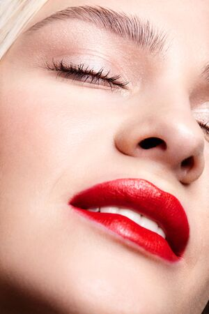 Closeup macro portrait of female part of face. Human woman with red smiling lips and beauty makeup. Eyes closed. Archivio Fotografico