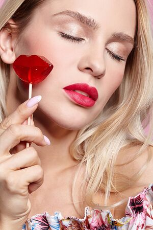 Blonde woman with closed eyes  holding candy on stick near face. Red female lips shape lollipop. Sweet tooth concept.
