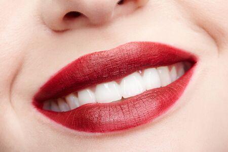Primer retrato macro de la parte femenina de la cara. Mujer humana roja sonriendo, labios con maquillaje de belleza de día. Chica con forma de labios perfecta. Foto de archivo