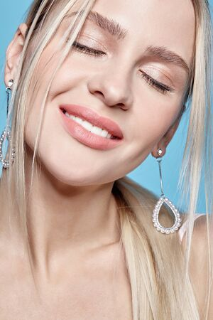 Portrait of beautiful young blonde woman with earrings. Blonde female with closed eyes on blue background.