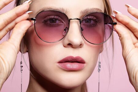 Close-up portrait of attractive young woman in tinted glasses. Female looking at camera on pink background.