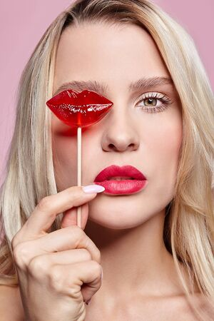 Portrait of blonde woman closing by candy her eye. Red female lips shape lollipop. Sweet tooth concept.