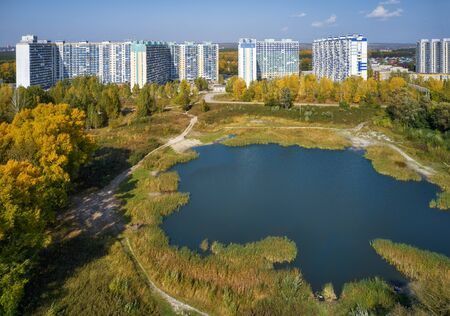 The area of new buildings in siberian town Novosibirsk. Bird's-eye aerial view on pond in the autumn park and on town with modern residential buildings. Odoevskogo street, Beresovoe, Novosibirsk, Siberia, Russia. Фото со стока