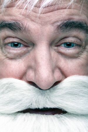 Close-up of the face of a Santa Claus. White-haired elderly man with white beard and moustache looking in camera.
