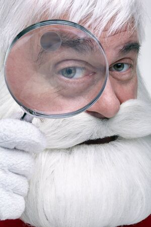Close-up of the face of a Santa Claus. White-haired elderly man with white beard and moustache looking in camera through a magnifying glass