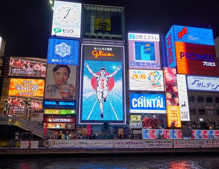 OSAKA, JAPAN - OCTOBER 14, 2019: The bright and flashy billboards along the Dotonbori canal with the symbol of the city, the Glico Running Man at night. Osaka. Japan
