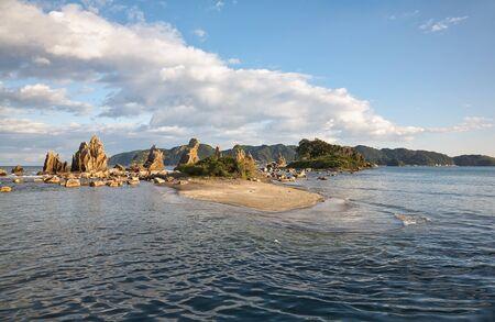 Hashigui-iwa (Bridge Pillar Rocks) - the series of rocks leading towards Oshima Island near Kushimoto at the sunset light. Wakayama prefecture. Honshu. Japan