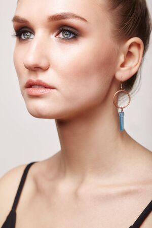 Beauty portrait of young female with galvanic earring in form of blue crystal.