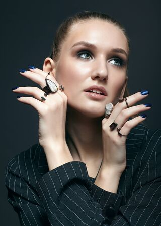 Beauty portrait of young female with blue manicure on dark background. Young beautiful woman with many bijouterie rings with stones on fingers. Girl with hands near face
