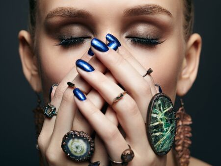 Beauty portrait of young female with eyes closed and blue manicure on dark background. Young beautiful woman with many bijouterie rings with stones on fingers. Girl with hands near face