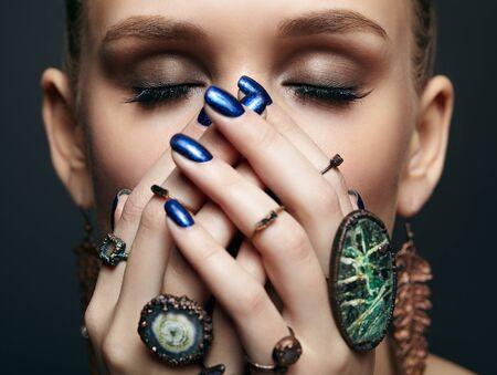 Ritratto di bellezza di giovane donna con gli occhi chiusi e manicure blu su sfondo scuro. Giovane bella donna con molti anelli di bigiotteria con pietre sulle dita. Ragazza con le mani vicino al viso
