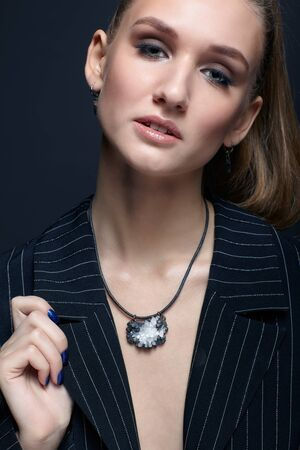 Beauty portrait of young female with blue manicure on dark background. Young beautiful woman with brooch.