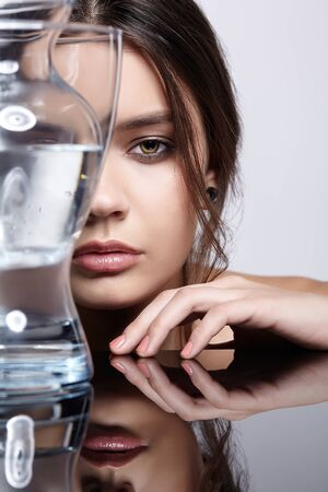 Girl hides her face behind a glass vase with water. Beauty portrait of young woman at the mirror table. Female on gray background. Banco de Imagens