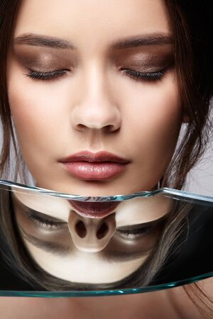Portrait of a beautiful girl with reflection in a mirror splinter. Female with mirror shard posing on gray background. Eyes closed.
