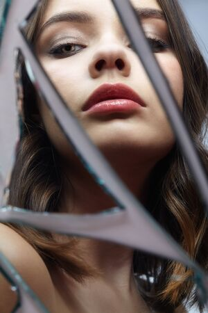Young woman looks in a broken mirror. Portrait of beautiful female in the mirror shards.