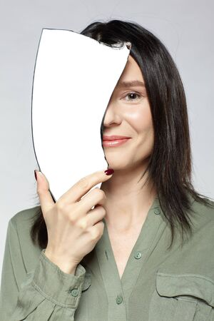 Smiling female with a shard of the mirror. Young woman with mirror splinter in hand posing on gray background. 版權商用圖片