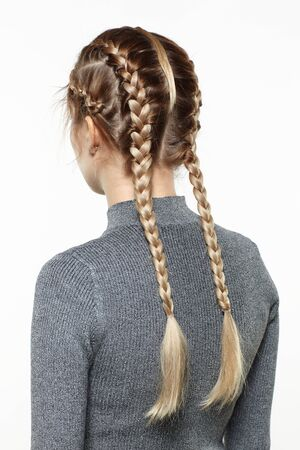 Back view portrait of beautiful young dark blonde woman. Female with creative braid hairdo on gray background.