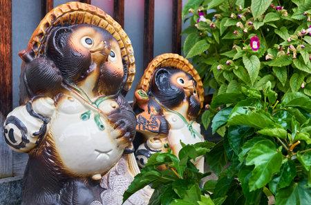 KYOTO, JAPAN - OCTOBER 18, 2019:  Ceramic statues of two Bake-danuki near the Japan's bar. They are the kind of folklore supernatural beings (tanuki yokai ) revered as kami, ensuring success in trade. 에디토리얼