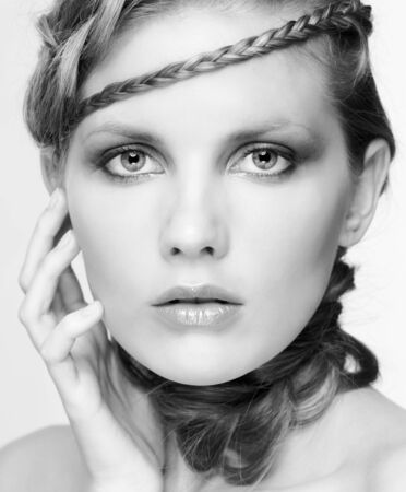 Black and white portrait in high key tone of beautiful young dark blonde woman with creative braid hairdo touching her face