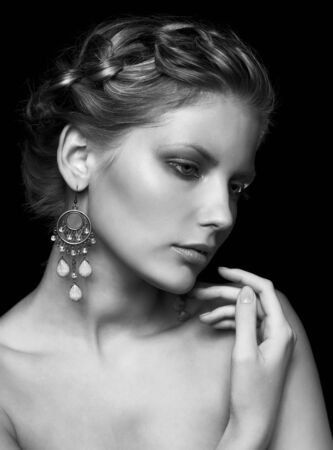 Black and white portrait in dark key tone of beautiful young woman  touching her shoulder