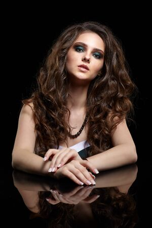 Beauty portrait of young woman sit at the black table. Brunette girl with long hair and evening female makeup on black background.