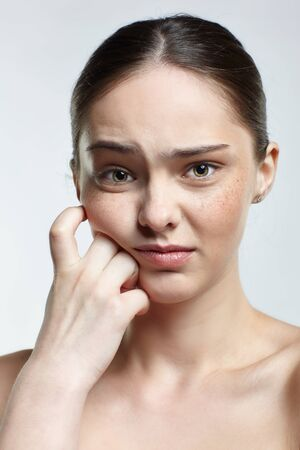 Emotional young woman face portrait with dissatisfied facial expression. Human female natural emotions and expressions concept. Girl with oothache pain on white background. Banco de Imagens