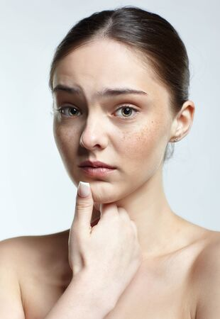 Emotional young woman face portrait with unhappy facial expression. Human female natural emotions and expressions concept. Girl with clean, healthy skin and nude makeup posing on white background.