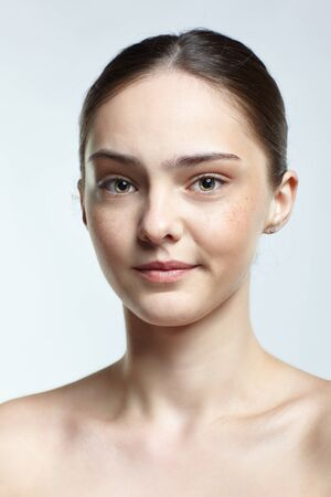 Emotional young woman face portrait with displeased facial expression. Human female natural emotions and expressions concept. Girl with clean, healthy skin and nude makeup posing on white background.