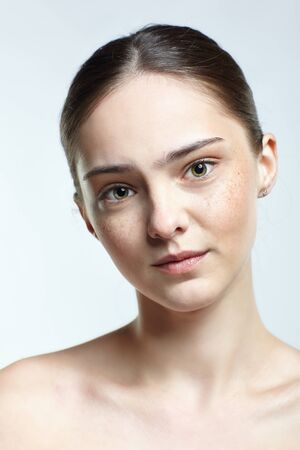 Emotional young woman face portrait with calm and tender facial expression. Human female natural emotions and expressions concept. Girl with nude makeup posing on white background. Banco de Imagens